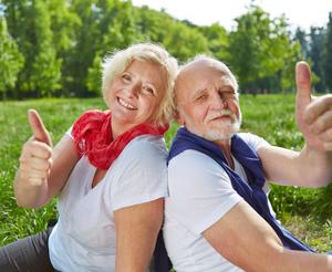 Zwei zufriedene Senioren halten Daumen hoch in der Natur